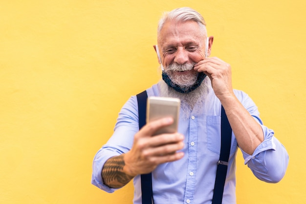 Modny modniś mężczyzna używa telefon komórkowego robi rozmowie wideo podczas gdy będący ubranym mody jedwabniczą maskę bezpieczeństwa