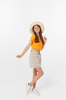 Modny modniś portret młoda stylowa nastoletnia dziewczyna pokazuje ona ręki, pozytywny nastrój i emocje, podróżuje samotnie. pojedynczo na szarym tle