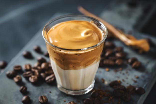 Modny napój kawowy dalgona z mlekiem i bitą pianką z kawy rozpuszczalnej i cukru.