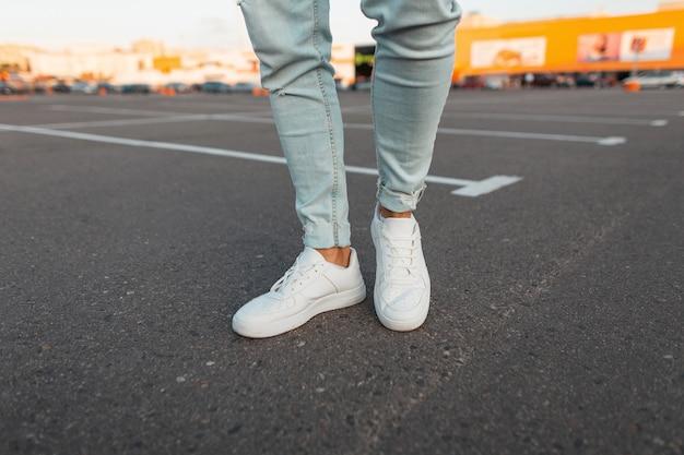 Modny, nowoczesny młody mężczyzna w stylowych niebieskich dżinsach w modnych skórzanych sezonowych białych trampkach stoi na parkingu w mieście. zbliżenie męskich stylowych nóg. letni wygląd.