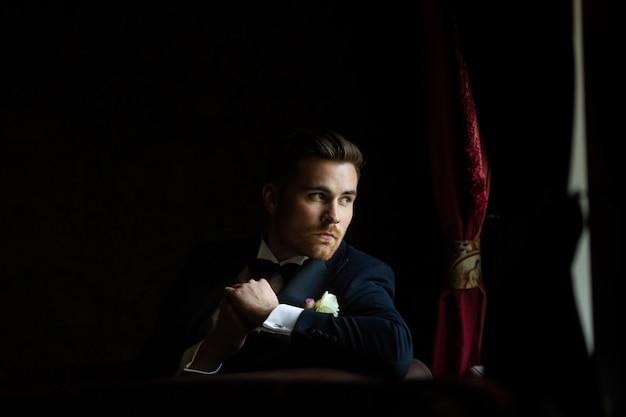 Modny pan młody oczekuje panny młodej przy oknie. portret pana młodego w czarnym garniturze