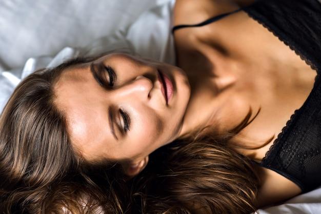 Modny poranny portret seksownej niesamowitej młodej brunetki, leżącej na łóżku, noszącej bieliznę i relaksującej, luksusowego stylu życia, naturalnego piękna, zielonych oliwkowych oczu, opalonej idealnej sylwetki.