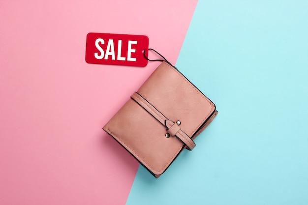 Modny portfel skórzany z czerwoną metką sprzedażową na różowo niebieskim .. rabat. minimalizm