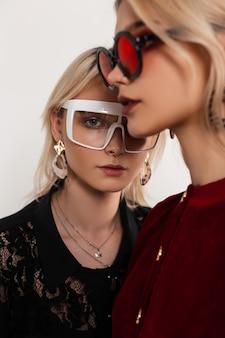 Modny portret dwóch nastoletnich dziewcząt w kolorowych okularach z blond włosami w czerwono-czarnych sukienkach stojących w pobliżu starej szarej ściany