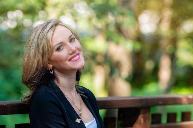 Modny portret eleganckiej, miłej, uśmiechniętej blondynki na rozmytym tle parku