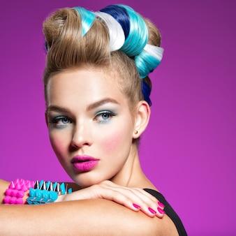 Modny portret młodej modelki rasy kaukaskiej z jasnym makijażem piękna kobieta z kreatywną fryzurą kobieta z portret dziewczynki z bransoletkami na rękach