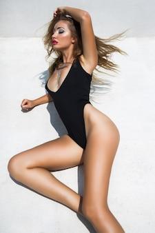 Modny portret oszałamiającej seksownej kobiety o idealnie opalonym ciele, artystycznym makijażu, siedzeniu na podłodze, czarnym bikini, minimalistycznym stylu, stonowanych kolorach.