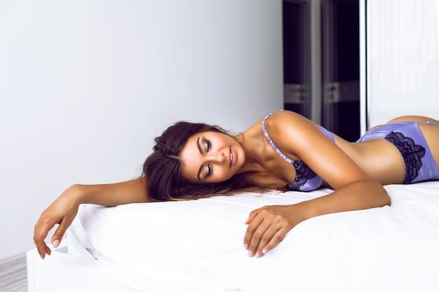 Modny portret pięknej, zmysłowej kobiety o idealnym ciele i seksownej jedwabnej bieliźnie, ciesz się porankiem i zrelaksuj się w dużej białej sypialni.