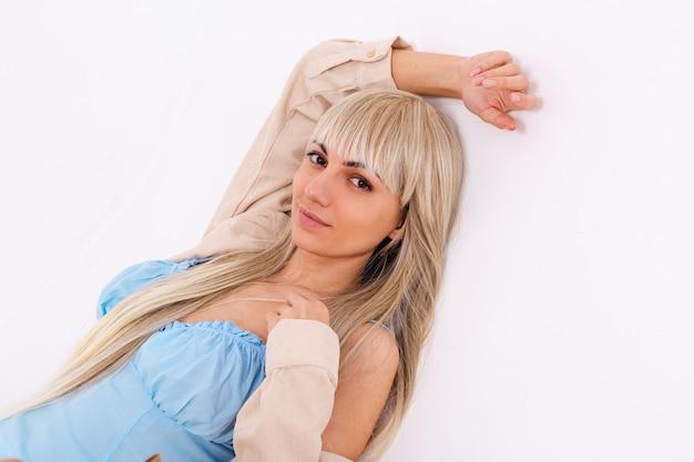 Modny portret szczupłej blondynki z długimi szykownymi włosami w jasnoniebieskiej sukience i sztruksowej koszuli