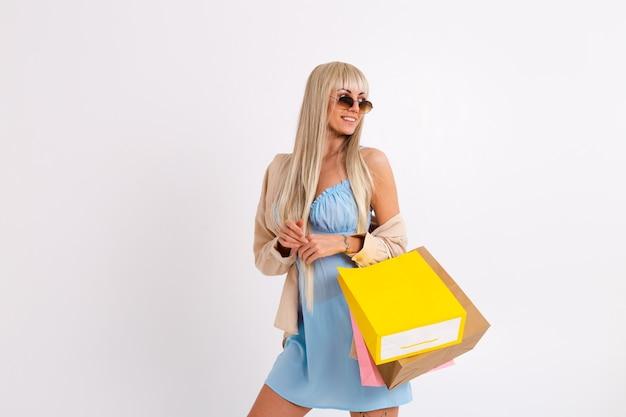 Modny portret szczupłej blondynki z długimi włosami w jasnoniebieskiej sukience i sztruksowej koszuli