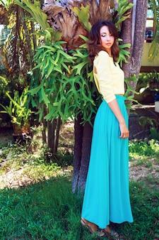 Modny portret zmysłowej, pięknej brunetki, z niesamowitymi długimi włosami i jasnym makijażem, pozująca w pobliżu egzotycznych roślin w letni dzień, ubrana w luksusową jedwabną jasną sukienkę i naszyjnik.