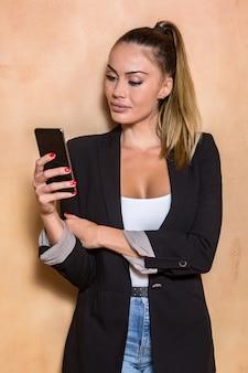Modny przedsiębiorca przegląda smartphone blisko ściany