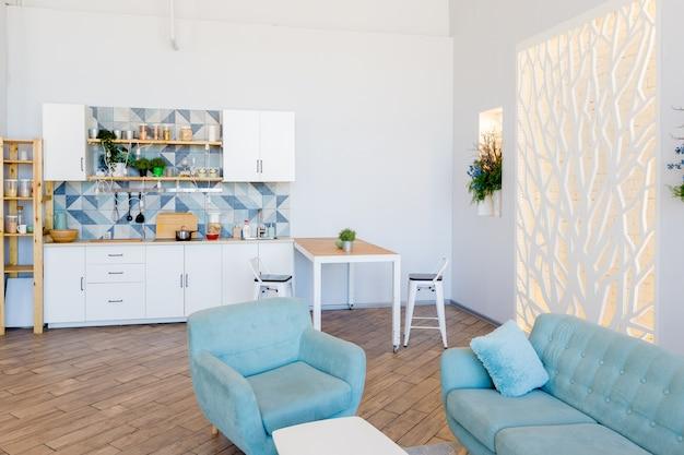 Modny przestronny apartament o stylowym wystroju w pastelowych kolorach zieleni, szarości i bieli z dużym oknem i dekoracyjnymi ścianami. sypialnia i kuchnia