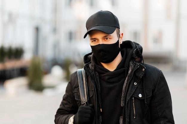 Modny przystojny facet w masce ochronnej i czarnej czapce w stylowej bluzie z kapturem i kurtce z plecakiem spaceruje po ulicy. covid-19 i koncepcja pandemii