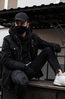 Modny przystojny mężczyzna w czarnej masce ochronnej i stylowej czarnej makiety odzieży z czapką, kurtką i bluzą z kapturem siedzi na ulicy. miejski nowoczesny styl odzieży męskiej
