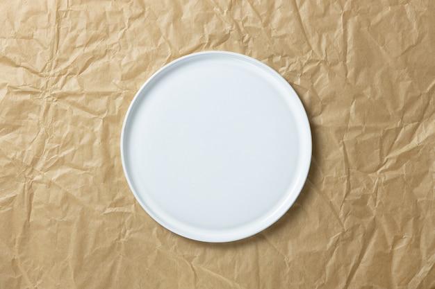 Modny pusty biały okrągły talerz z prostymi krawędziami na zmiętym papierze rzemieślniczym, płaski układ w minimalistycznym stylu, miejsce na kopię.