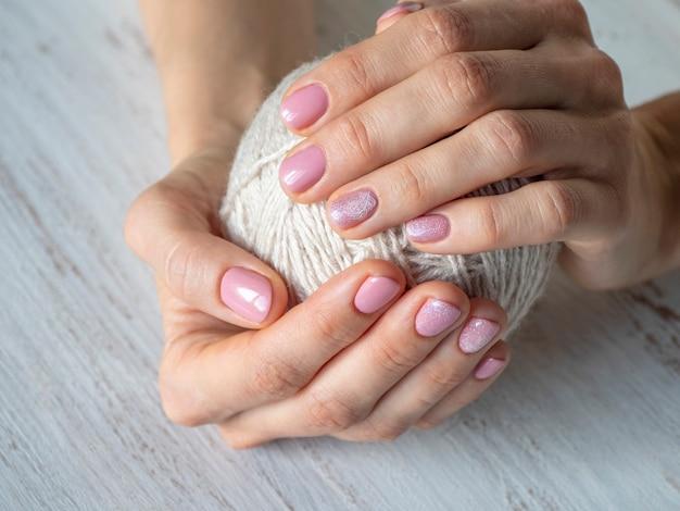 Modny różowy wzór do manicure w dłoni. ręce są owinięte wokół kłębka wełny.
