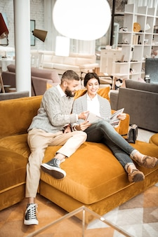 Modny sklep meblowy. uśmiechnięta, rozpromieniona kobieta czytająca katalog mebli siedząc na kanapie z mężem w pobliżu