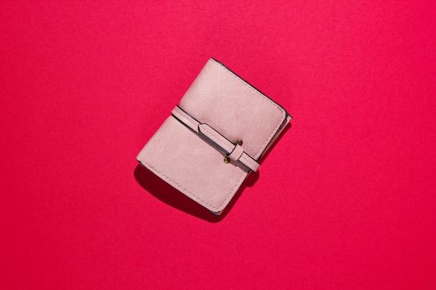 Modny skórzany portfel na czerwonej powierzchni.