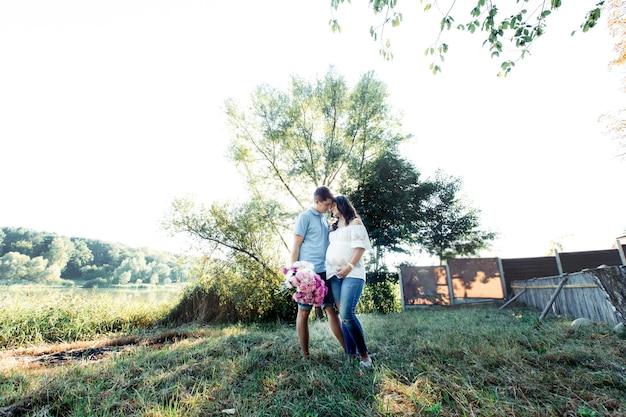 Modny spodziewający się para stoi w ciepłych objęciach pod zielonym drzewem