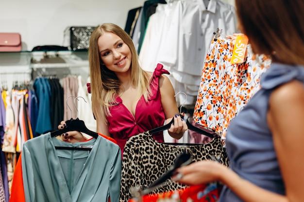 Modny sprzedawca pokazuje dziewczynie sukienkę i tygrysią bluzkę