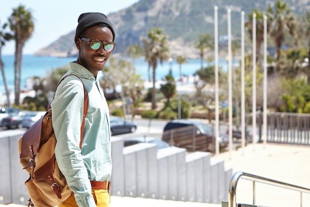 Modny student w kapeluszu i okularach przeciwsłonecznych, cieszący się słoneczną, ciepłą pogodą