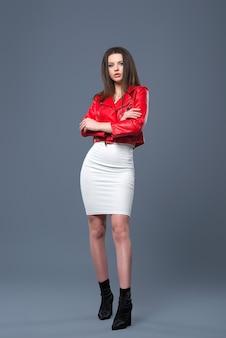 Modny styl, modna odzież damska, kombinacja kolorów. piękna brunetka dziewczyna w białej sukni i czerwonej skórzanej kurtce na białym tle szarym tle.
