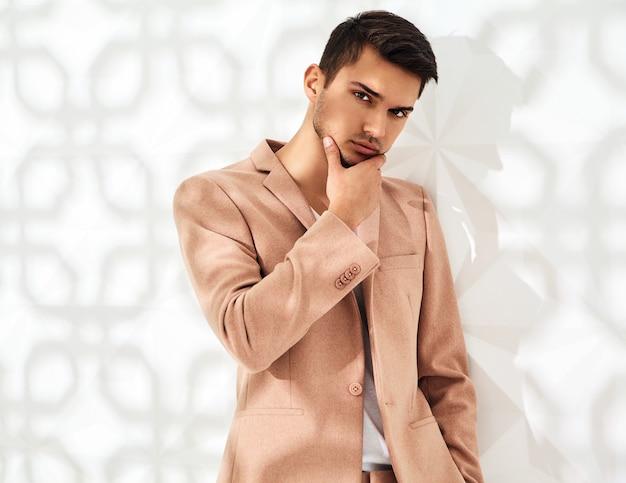 Modny stylowy model ubrany w elegancki jasnoróżowy garnitur