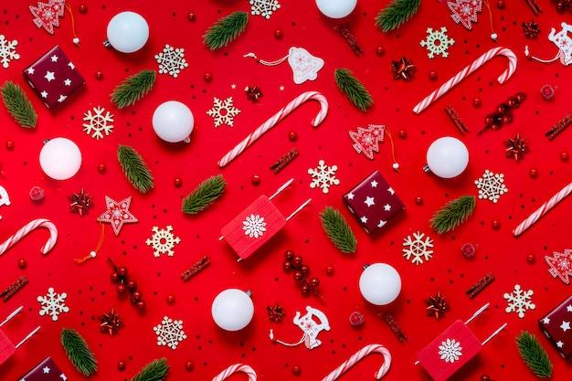 Modny świąteczny wzór z zabawkami zimą i nowym rokiem na czerwonym tle.