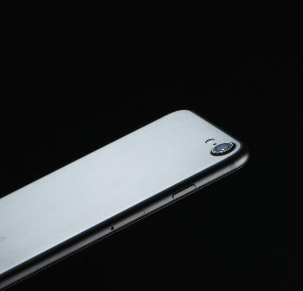 Modny telefon z ekranem dotykowym i aparatem na czarnym tle technologii tekstury