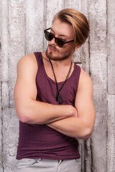 Modny wygląd. przystojny młody mężczyzna w okularach przeciwsłonecznych, oparty o ścianę i odwracający wzrok