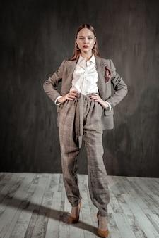 Modny wygląd. śliczna brunetka kobieta ubrana w ciepły kostium podczas prezentacji swojego wyboru
