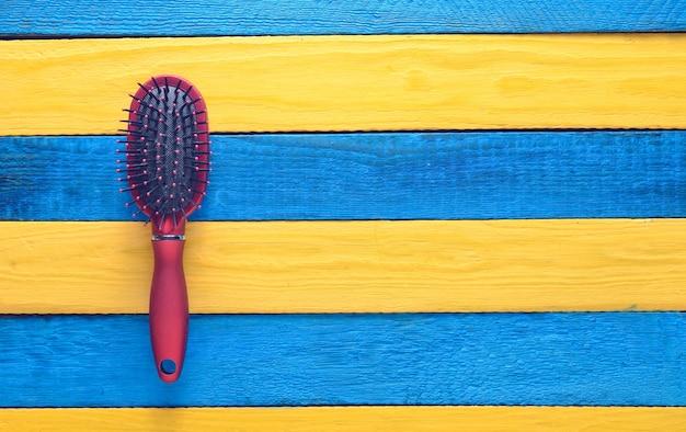 Modny żeński grzebień do pielęgnacji włosów na żółtym niebieskim drewnianym stole. trend minimalizmu. skopiuj miejsce widok z góry. koncepcja lato.