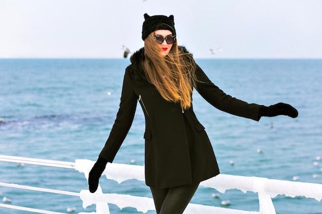 Modny zimowy portret eleganckiej blondynki, ciesz się zimnym śniegiem nad morzem, lodem i wietrznie, czarnym płaszczem, zabawną czapką, długimi włosami, zmysłowym nastrojem, samotną podróżą, zimową modą.
