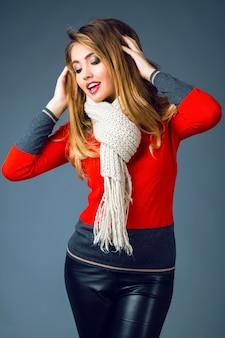 Modny zimowy portret pięknej blondynki z seksownym dymnym makijażem, ubrana w jasny modny elegancki swobodny sweter, czarne skórzane spodnie i duży przytulny ciepły beżowy szal.