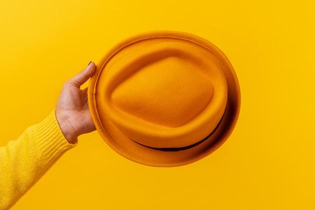 Modny żółty filcowy kapelusz w ręku na żółtym tle