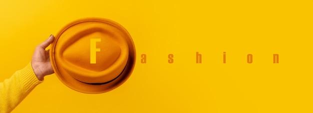 Modny żółty filcowy kapelusz w ręku z napisem moda na żółtym tle, panoramiczny obraz