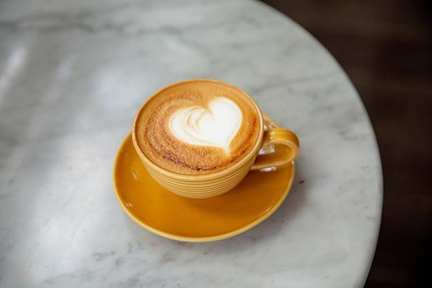 Modny żółty kubek gorącego cappuccino na tle marmurowego stołu.