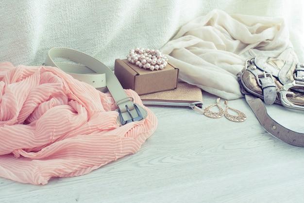 Modnych akcesoriów szalika paska torebki biżuteria na drewnianym lekkim tle