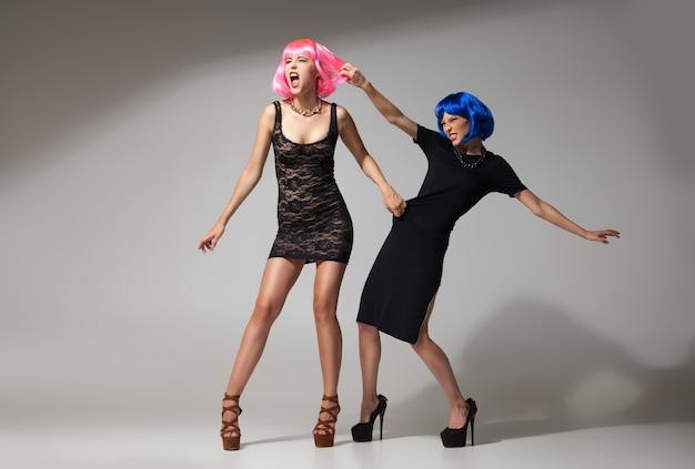 Modowa bitwa dwóch modelek w jasnych perukach i czarnych sukienkach.studio zdjęć