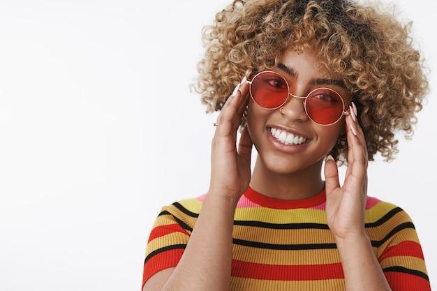 Modowa diva gotowa na spacer. przystojna, stylowa i szczęśliwa afroamerykanka z blond kręconymi włosami w modnych okrągłych okularach przeciwsłonecznych, pochylająca głowę dotykająca ramek i uśmiechająca się szeroko do kamery