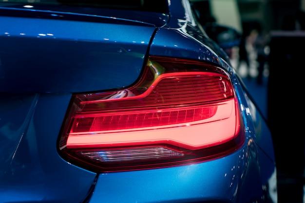 Modren niebieski samochód z czerwonym światłem na drodze w nocy.