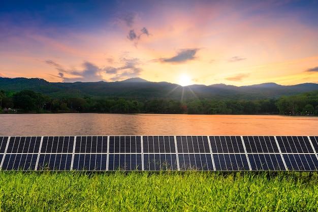 Moduły fotowoltaiczne elektrownia słoneczna z widokiem na jezioro zielona zalesiona góra z wieczornym niebieskim dramatycznym tle zachodu słońca na niebie