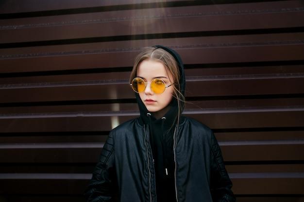Mody dzieciaka pojęcie - elegancki dziewczyny dziecko jest ubranym czarnych przypadkowych ubrania i okulary przeciwsłonecznych pozuje lato w mieście
