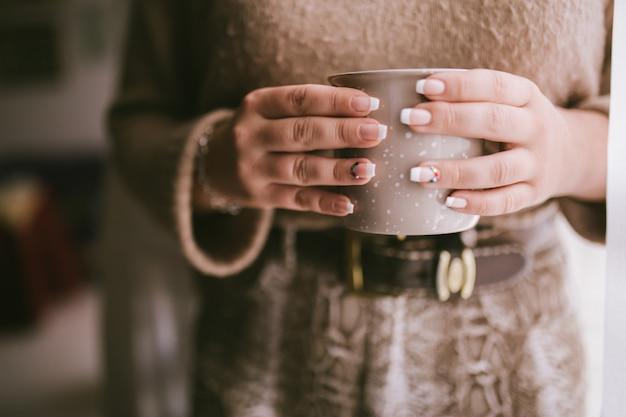 Mody kobieta cieszy się kawowego lub herbacianego moment.