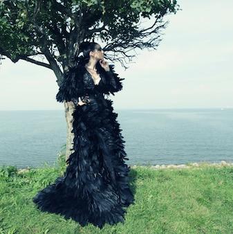 Mody kobieta pozuje blisko morza.