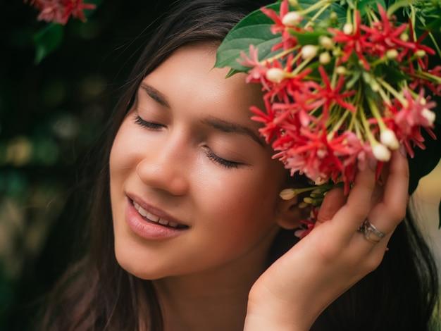Mody piękna żeński portret z czerwonymi kwiatami