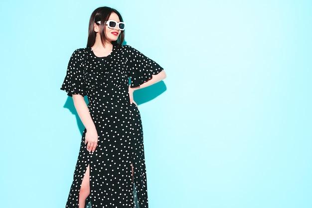 Mody portret młodej pięknej brunetki ubranej w ładną modną letnią sukienkę w kropki