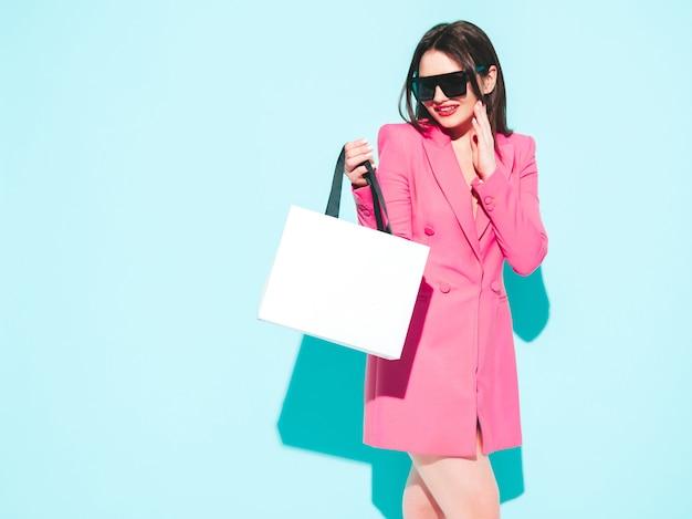 Mody portret młodej pięknej brunetki ubranej w ładny różowy letni garnitur