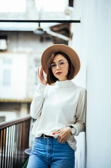 Mody ulicznej zainteresowana kobieta nosi kapelusz, niebieskie dżinsy, szeroki kapelusz i okulary transperent na balkonie